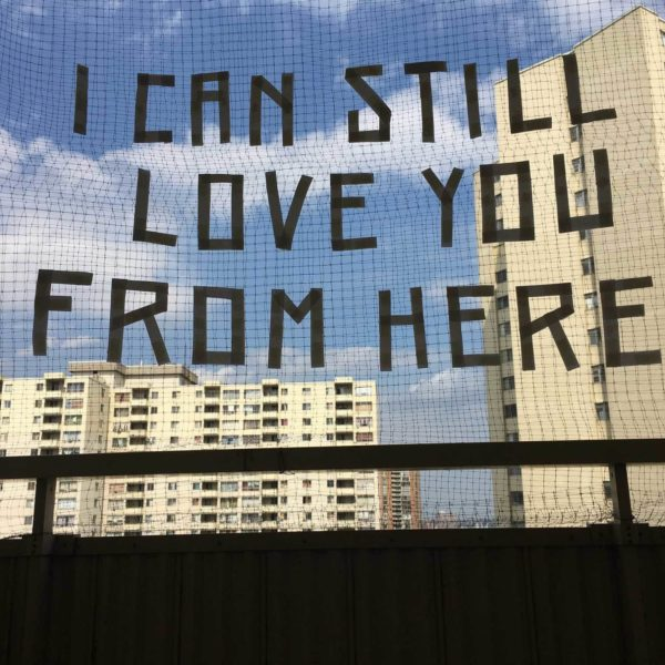 "Image description: A photograph of an outdoor fence with entitled text ""I can still love you from here"" with a background view of two concrete housing complex skyscrapers."